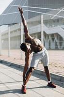 Bel homme afro-américain fait des étirements avant un entraînement à l'extérieur