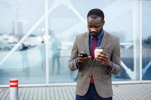 heureux, homme afro-américain, lire quelque chose dans son smartphone photo