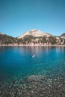 homme solo flottant sur la mer bleue entourée de montagne photo