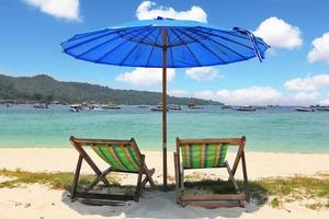 parasol bleu et chaises longues à rayures