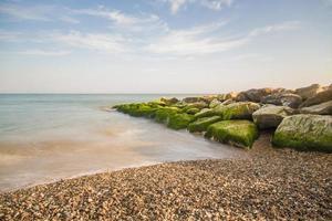 Jetée de pierre de la plage de galets le jour de l'été uk