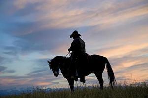 silhouette de cow-boy contre le ciel de l'aube. (voir d'autres dans mon portfolio / lightbox) photo