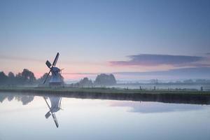 Moulin à vent par rivière au lever du soleil