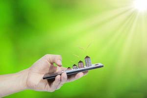 main tenant le smartphone avec des pièces de monnaie et des plantes photo