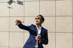jeune homme d'affaires jette des dollars et danse dans la rue