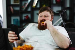 L'homme vérifie son smartphone alors qu'il est assis sur le canapé et mange photo