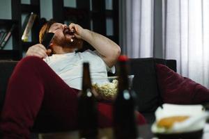 gros homme mange du pop-corn sur le canapé photo