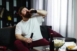 gros homme boit de la bière allongé sur le canapé photo