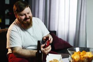 Heureux gros homme en chemise sale joue à des jeux vidéo photo