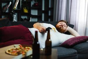 gros homme se trouve sur le canapé et regarde la télévision photo