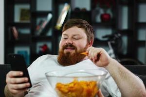 homme mangeant des chips tout en vérifiant son téléphone