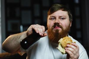 gros homme regarde la télévision, mange un hamburger et boit de la bière