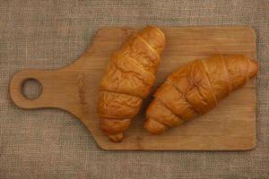 Croissants sur une planche à découper sur fond de sac