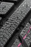 Gros plan de pneu de voiture avec des gouttes d'eau