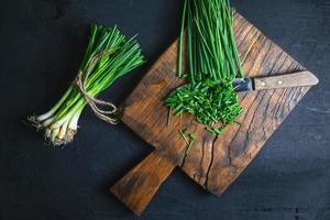 Oignon vert frais coupé sur planche à découper en bois