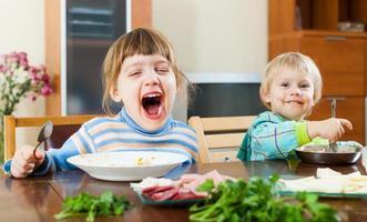 Bébés filles mangeant de la nourriture à table photo