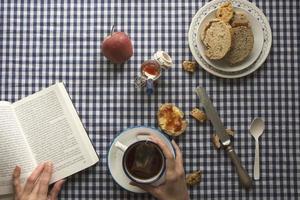 femme prenant son petit déjeuner, ses mains et un livre photo