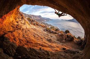 Grimpeur mâle escalade le long d'un toit dans une grotte photo