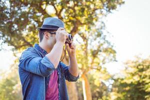 beau hipster à l'aide d'un appareil photo vintage