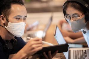 équipe de travailleurs créatifs portant des masques faciaux