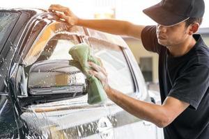 L'homme lave une voiture au lave-auto photo