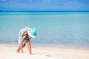 fille jouant dans le sable sur une plage photo