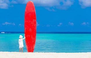 fille debout avec une planche de surf rouge photo