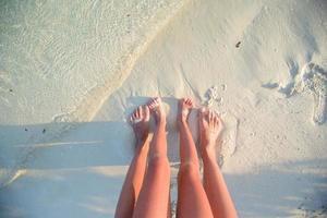 Gros plan des pieds de deux personnes sur une plage photo