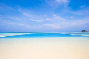 piscine à débordement sur une plage tropicale photo