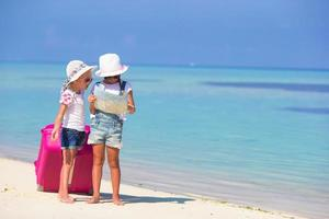 deux filles avec une carte et des bagages sur une plage