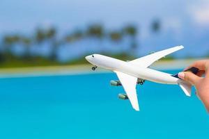 Petit avion jouet blanc contre une mer turquoise