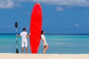 couple avec un paddleboard à la plage photo