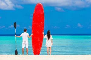 deux personnes debout sur une plage avec un paddleboard photo