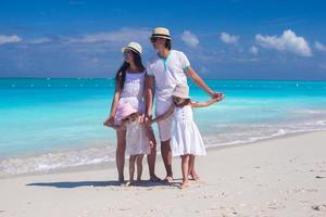 famille de quatre personnes sur une plage de sable blanc photo