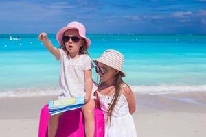 sœurs avec une carte et une valise sur une plage