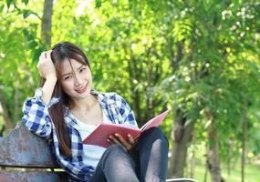 femme asiatique, lecture livre, dans parc