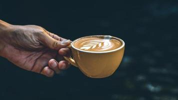 main tenant un latte dans une tasse jaune