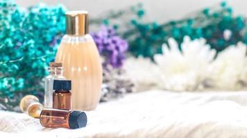 bouteille d'huile essentielle. phytothérapie ou flacon compte-gouttes d'aromathérapie isolé sur fond blanc. fleurs de romarin frais et huiles essentielles sur la table photo