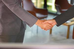 hommes d & # 39; affaires faisant la poignée de main au bureau