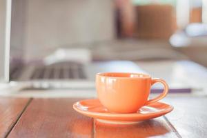 Tasse à café orange sur un poste de travail