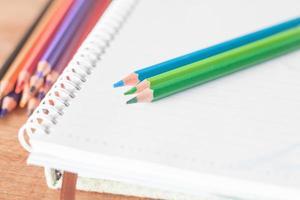 gros plan, de, crayons colorés, sur, a, cahier à spirale photo