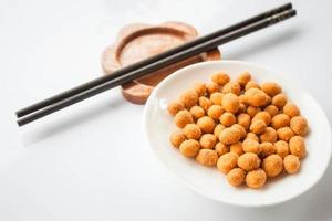 Snack aux arachides enrobé d'un assaisonnement épicé avec des baguettes photo