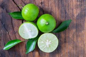 Citrons verts mûrs frais sur fond de bois