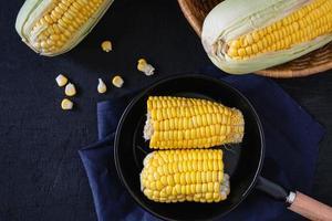 Maïs frais cru dans la poêle sur fond noir photo