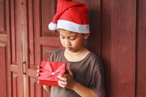 garçon avec boîte-cadeau le jour de noël photo