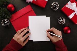 mains écrivant une maquette de carte de voeux blanche