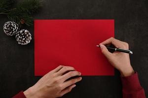 mains écrivant une maquette de carte de voeux rouge