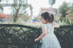 fille de trois ans douce, heureuse et souriante jouant dans un parc en plein air photo