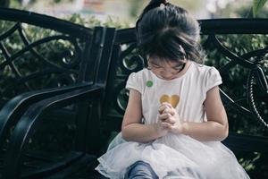 Fille de trois ans prie Dieu au parc à l'extérieur