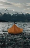Kayak orange sur le sable gris près du plan d'eau pendant la journée
